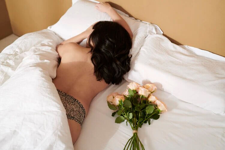 Woman in floral bikini lying on bed